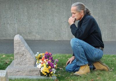 お墓の前でひざまずく男性