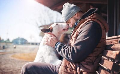 額を寄せる男性と犬