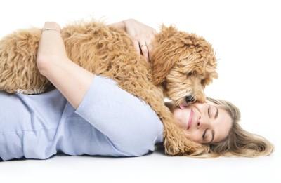 横になった女性の上に乗っかってキスする犬