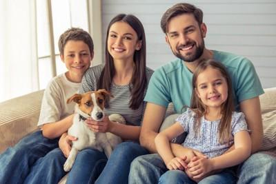 ソファーに座る家族と子犬