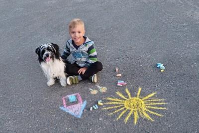 チョークで落書きされた地面に男の子と一緒に座る犬