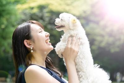 笑顔で犬を抱き上げる女性
