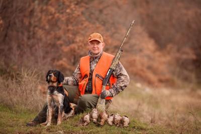 一緒に狩りをしている犬と人