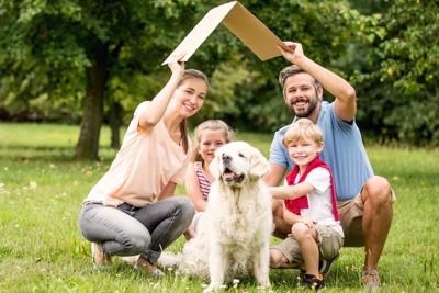 屋根の模型を持った家族と犬