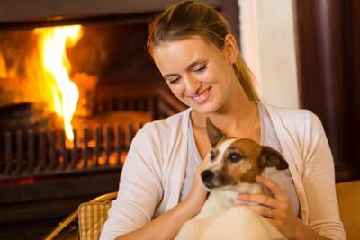 暖炉の前でくつろぐ女性と犬