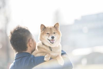 男性に抱っこされている柴犬