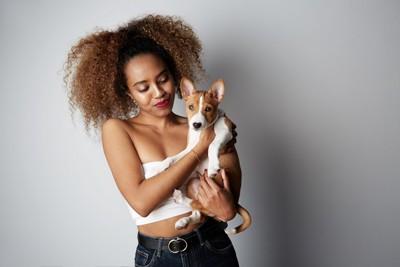 女性に抱っこされる犬