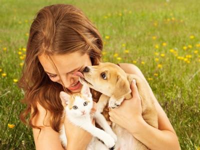 犬と猫を抱きしめる女性