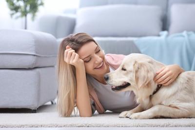 女性の隣に伏せる犬