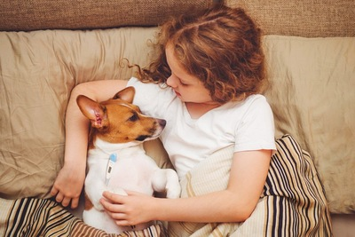 天然パーマの白人の女の子に看病をされながら体温を計測している犬