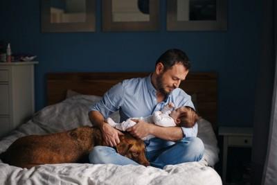 赤ちゃんを抱く男性とそばにいる犬