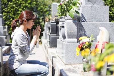 墓に手を合わせる女性
