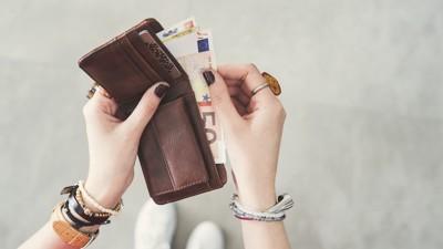 ブラウンのお財布を持つ手