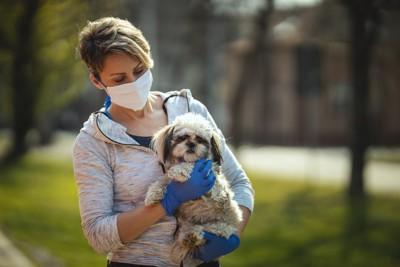 シーズーを抱くマスクと手袋を着けた女性