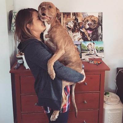 女性に抱きかかえられる犬