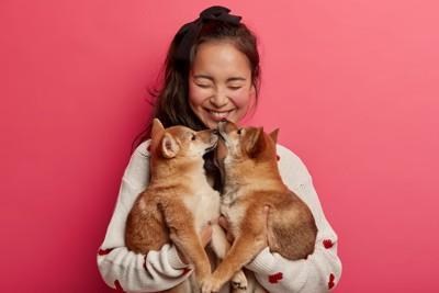 女性の顔を舐める2匹の柴犬