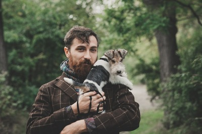 犬を抱っこしているヒゲの男性