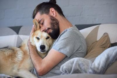ベッドで犬を抱きしめる男性