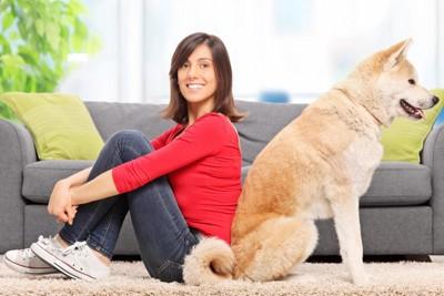 飼い主と背中合わせに座る犬