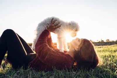 芝生に寝そべる女性と犬