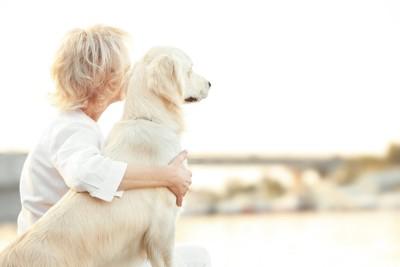 肩を寄せ合う犬と女性