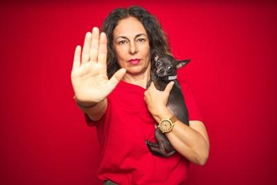 NOと手を突き出す犬を抱いた女性