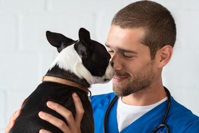 獣医さんに鼻先をくっつける犬