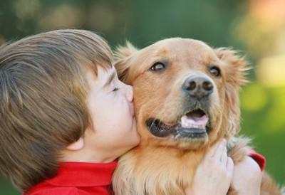 犬にキスをしている子供