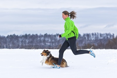 女性と雪の中を走る犬