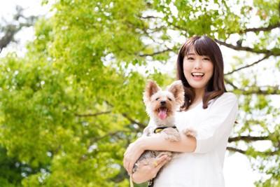 笑顔で小型犬を抱く若い女性