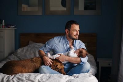 赤ちゃんを抱っこするお父さんに寄り添う犬