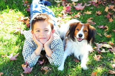 草の上で犬と並んでいる男の子