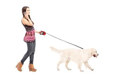 犬の散歩中に電話をする女性