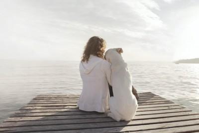 女性と並んで座ってもたれかかる白い犬の後ろ姿