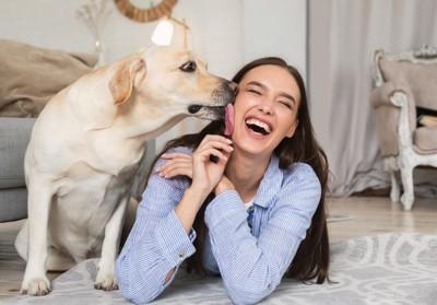 女性の顔を舐める大型犬