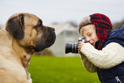 犬をカメラで撮影する男の子