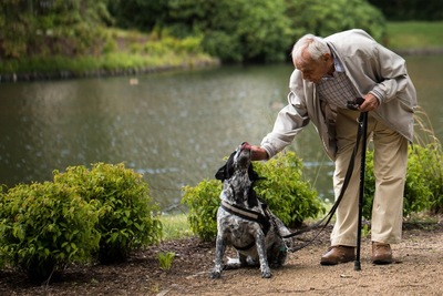 杖を持つ男性と白黒の犬