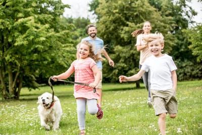 笑顔で犬の散歩をする家族