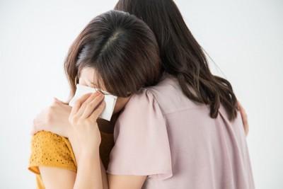 泣く女性を励ます女性