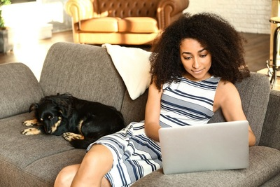 ソファーでくつろぐ犬と女性