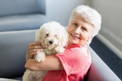 白い小型犬を抱く女性