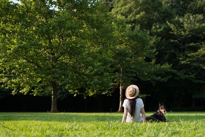 芝生でゆったりする女性と犬