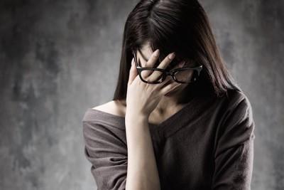 顔を押さえて悩む女性