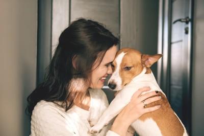 白茶の犬と頭を合わせて抱っこする女性