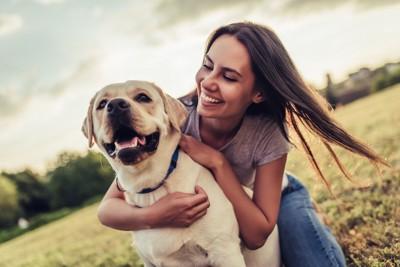 犬を抱きしめる笑顔の女性
