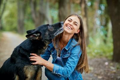 しゃがんだ女性にキスする犬