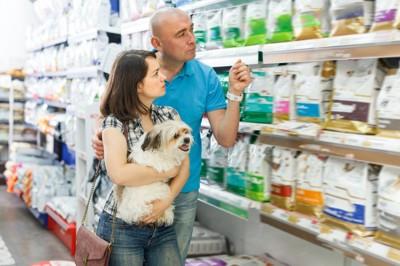 犬を抱いて買い物している男女
