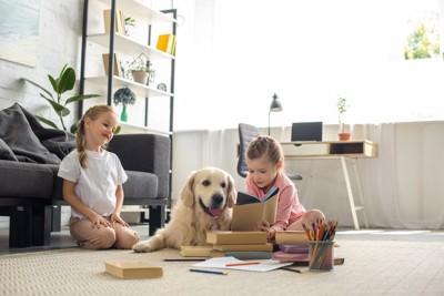 室内で犬に絵本を見せる2人の女の子
