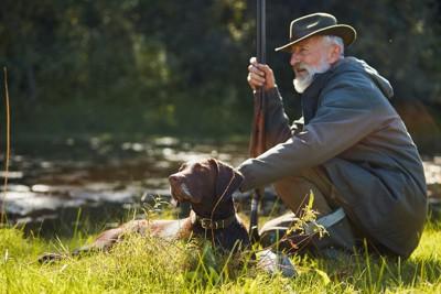 猟銃を持った男性と猟犬