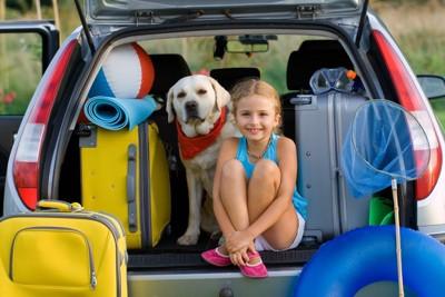 子どもと一緒に車に乗る犬